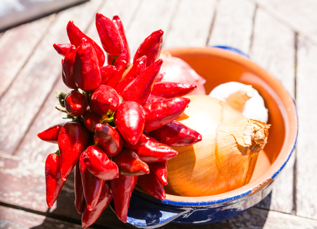 Cooking: onion, garlic and chilli in a dish on top of a wooden table