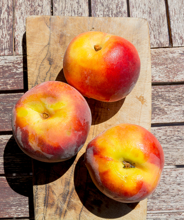 Three peaches on a cutting board: in table fruit