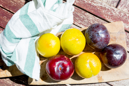 table fruit: red and yellow plums on a cutting board. View from above