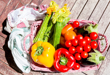 Zucchini, eggplant, peppers and tomatoes in a basket on a wooden board. Cooking with vegetables and greens