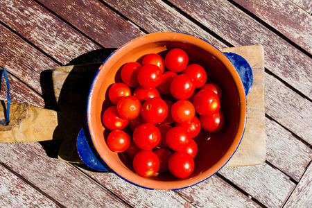 Tomatoes in a bowl on wooden table, with top view