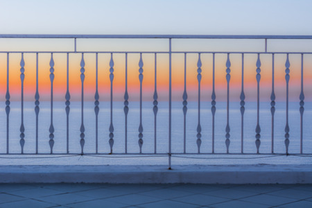 Sunset on the sea, with the railing of a terrace in the foreground