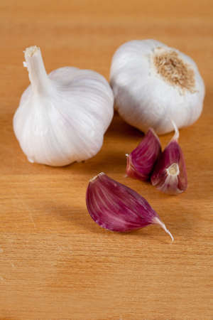 garlic clove: Two garlic bulbs with three cloves isolated on wood background Stock Photo