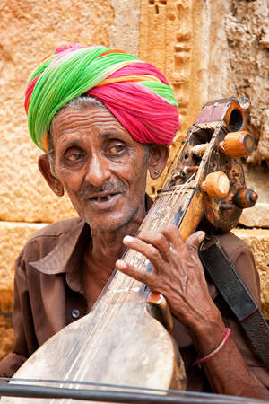 veiled: JAISALMER, INDIA - AUGUST 12   Unidentified musician playing Sitar on street  The Sitar is a plucked stringed instrument widely used in Indian classical music