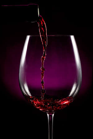 Red wine pouring on black background photo