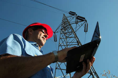 Engineer using laptop under the high voltage tower  Selective focus  photo