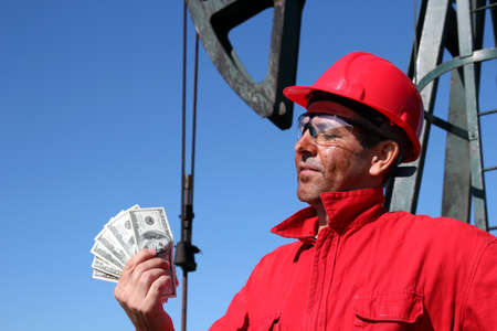 Oil Worker With Dirty Face Holding US Dollar Bills  photo