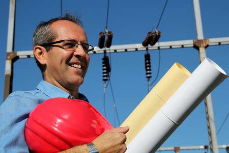 electrical engineer: Ingeniero sonriente con sombrero duro y Planos Foto de archivo