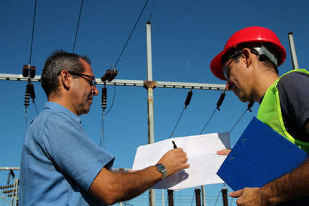 Engineer Showing Blueprint to Worker photo