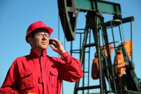 trabajador petroleros: Petr�leo Trabajador utilizando tel�fono celular en Siguiente para Pumpjack