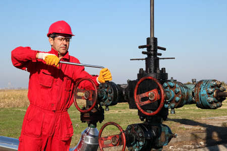 oil tool: Oil worker in safety gear with hand tool working on oil rig equipment   Stock Photo