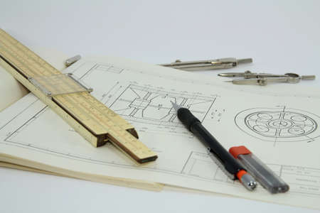 Slide rule and set of drawing instruments on a drawing isolated on white background  photo