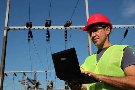 ingenieria industrial: Ingeniero con el equipo de protecci�n personal que pulsan en el teclado de la computadora