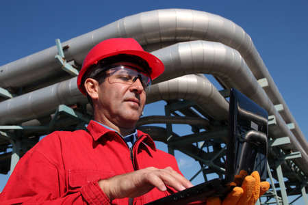 energetics: Industrial engineer inside oil and gas refinery using notebook