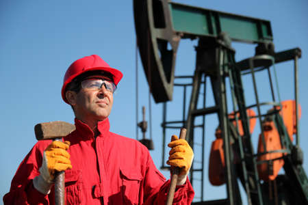 Oil industry worker standing next to pump jack, holding sledgehammer and crowbar  photo