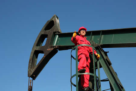 horsehead pump: Successful oil industry worker on the pump jack showing ok sign