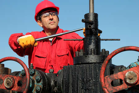 drilling rig: Oil industry worker with personal protective equipment using hand tool at oil well