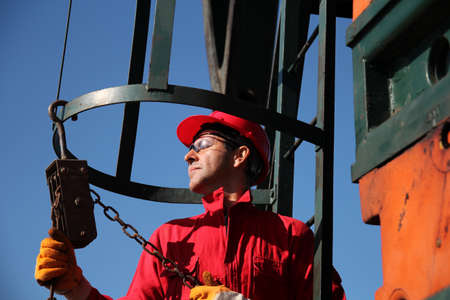 jack pump: Oil industry worker in action with chain winch at pump jack oil well