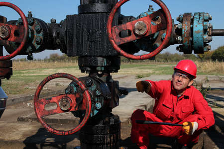 Oil worker pointing with his finger to oil field equipment
