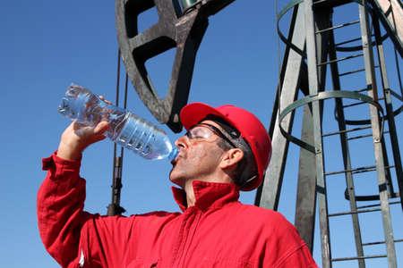 trabajador petroleros: Trabajador petrolero Sediento del agua potable de la botella en frente de la bomba de jack