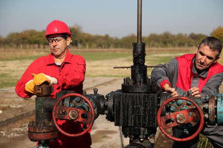 yacimiento petrolero: Dos ingenieros de petróleo y gas que trabajan en equipos de plataforma petrolera Foto de archivo