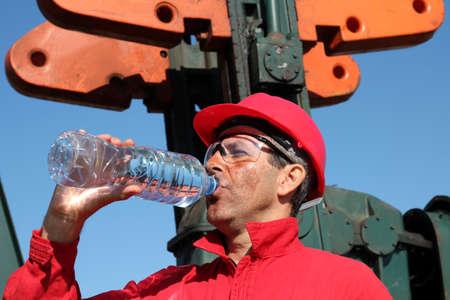 bomba de agua: Trabajador petrolero sed saciar con agua al lado de la bomba de jack