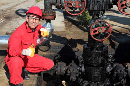 The oilfield worker squatting and showing thumbs up on oil rig  Stock Photo