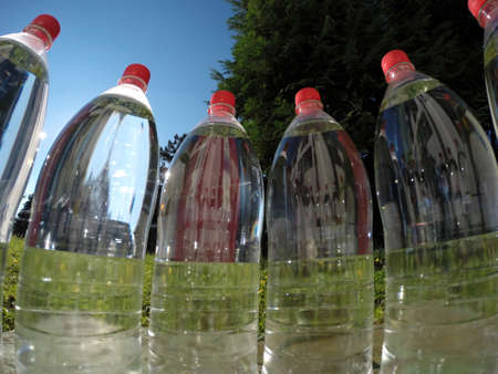 water view: Bottled water against a background of green nature. Stock Photo