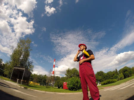 Industrial worker with cell phone against a blue sky with white clouds. photo