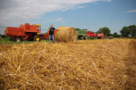 Agriculturist in a farm field with agricultural machinery photo
