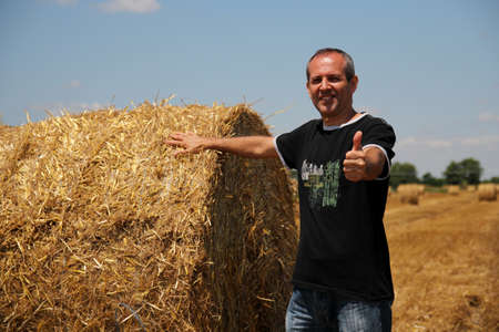 agriculturist: Smiling agriculturist in a farm field showing ok sign and hay bale Stock Photo