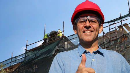 parget: Construction engineer with two construction workers working on scaffolding in the background showing thumbs up.