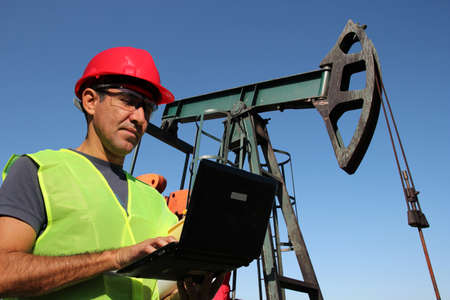 horsehead pump: Engineer with personal protective equipment typing on laptop computer in the oil field. Stock Photo