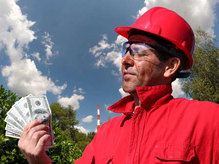 premises: Industrial worker holding US dollar bills in factory premises with factory chimney in the background. Stock Photo