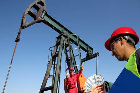 pozo petrolero: Dos trabajadores del petróleo en pozo de petróleo que sostiene billetes de un dólar de EE.UU. Foto de archivo