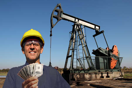 Oil worker or petroleum engineer holding US dollar bills in front of oil well. Best paid jobs concept Stockfoto