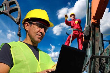 Ingegneri petroliferi nel giacimento petrolifero che registrano e aggiornano le informazioni sulle attività di produzione del petrolio con un computer portatile Archivio Fotografico