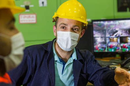 the two workers in protective masks and yellow helmets in control panel in the laboratory