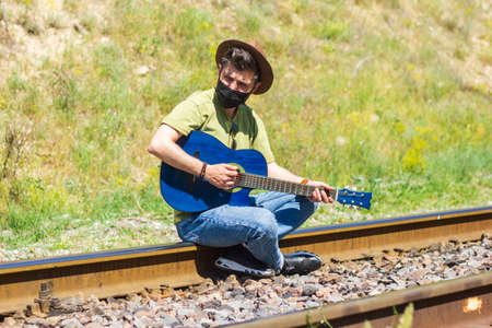 man with protective mask on railroad tracks playing on guitar Reklamní fotografie