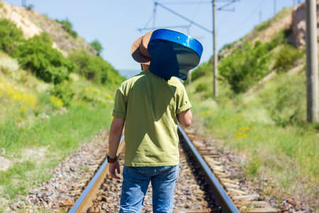 boy with blue guitar walking on railway Reklamní fotografie