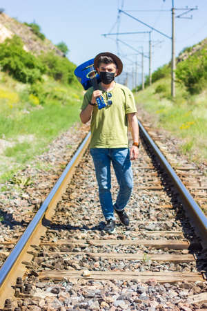 boy with blue guitar and black protective mask walking on railway