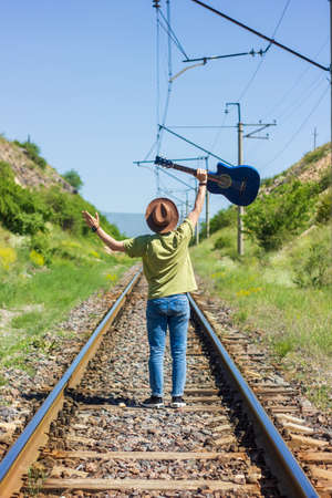 boy with blue guitar standing on railway