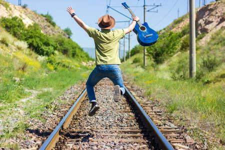 boy with blue guitar jumping on railway Reklamní fotografie