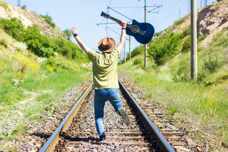 boy with blue guitar dancing on railway