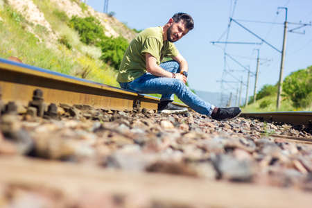 young lonely man sitting on rail lines Reklamní fotografie