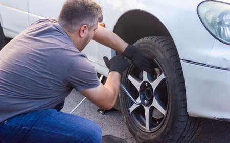 mechanic changing car wheel, car mechanic changing the wheel of a car