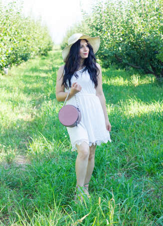 pretty fashion girl in straw hat in the park Stock Photo