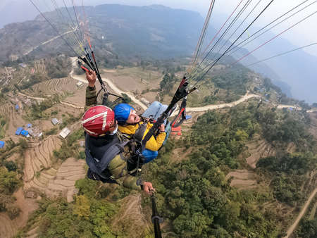paragliding in the mountains, the two persons on the top of the mountain, the parachutists are flying with a parachute Banque d'images