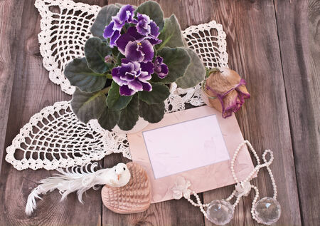 Retro composition with photo frame, knitted napkins and viola on a wooden background texture  photo