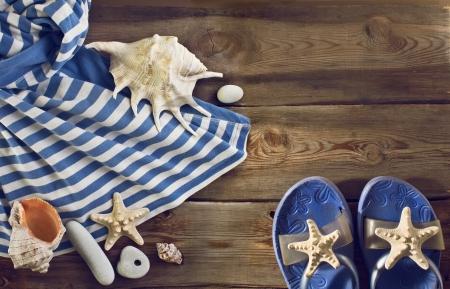 Beach flip flops, striped dress, seashells on a wooden floor. Summer vacations background Stock Photo - 25252188